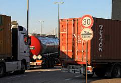 LKW-Stau vor der Zollgrenze in Hamburg Waltershof - ein Schild weist auf die Geschwindigkeitsbegrenzung von 30km/h sowie auf Zoll / Douane hin. Ein Tanklastzug und Auflieger mit Container warten auf die Weiterfahrt.