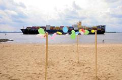 Sandstrand bei Hamburg Blankenese - bunte Luftballons; Reste eines Kinderfestes; auf der Elbe fährt ein Containerfrachter Richtung Hamburger Hafen.