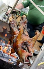 Spanferkel grillen auf dem Eppendorfer Landstrassenfest in Hamburg Eppendorf - glühende Holzkohle, Milchferkel am Spieß - junges Hausschwein,  dass noch gesäugt wird. Die Ferkel werden im Alter von ca. 6 Wochen geschlachtet.