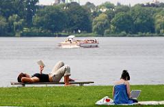 Entspannung am Ufer der Aussenalster - Ruhe vom Grossstadttrubel. Eine Frau liegt auf der Bank und liest ein Buch, eine andere sitzt auf der Wiese mit ihrem Labtop - im Hintergrund das Alstercabrio .