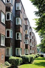 Fassade eines Klinkergebäudes - Vorgarten mit Sträuchern - Architektur in Hamburg Barmbek Nord.