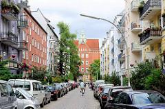 Blick durch eine schmale, dicht mit Autos zugeparkte Strasse zur Volksschule Lutherotstrasse - Bilder aus dem Hamburger Stadtteil Eimsbüttel.