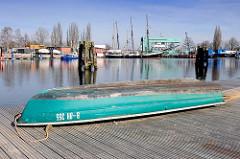 Blick über den Überwinterungshafen in Hamburg Harburg - ein Ruderboot liegt auf dem Ponton in der Sonne; im Hintergrund das Polizeigebäude der Wasserschutzpolizei - Wasserschutzpolizeikommisariat 3.