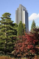 Sträucher und Bäume im Japanischen Garten von Planten un Blomen -  herbstlich gefärbte rote Blätter - Hotelgebäude am Dammtor, Hochhaus.