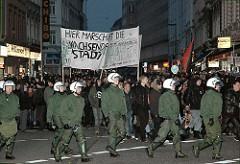 Demonstration auf der Sternschanze - Polizisten mit Helm begleiten den Demonstrationszug im Schulterblatt.
