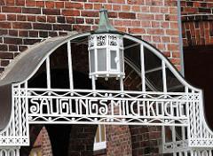 Eingang zur Säuglingsmilchküche - eiserne Schriftzeichen, Lampe am historischen Eingang Altonaer Kinderkrankenhaus.