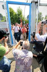 Die Stadtentwicklungssenatorin Anja Hajduk und Bezirksamtsleiter Markus Schreiber posieren mit Bolzenschneider für die Presse - der Durchgang durch den Zollzaun am Spreehafen in Hamburg Wilhelmsburg ist geöffnet worden. (2010)