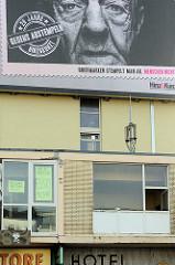 Fassade / Fenster am Spielbudenplatz in Hamburg St. Pauli, Instandhaltung -  Kein Abriss Essohäuser. Fassadenwerbung für Hinz & Kunzt - 20 Jahre gegen Abstempeln.