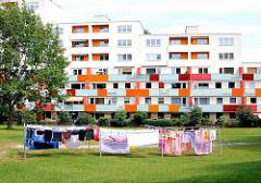 Bunte Wäsche trocknet an der Leine auf der grünen Wiese vor einem mehrstöckigen Wohngebäude im Hamburger Stadtteil Eißendorf, Bezirk Hamburg Harburg.
