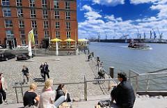 Terrasse in der Sonne an der Grossen Elbstrasse - Blick auf die Elbe und den Hamburger Hafen. Eine Hafenfähre fährt Richtung Finkenwerder - im Hintergrund Kräne der Werft.