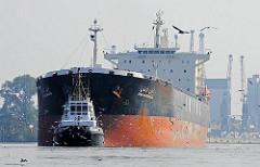 Der Bulkcarrier IRAN KHORASAN hat seine Ladung im Reiherstieg von Hamburg Wilhelmsburg gelöscht - die Lademarkierung ragt weit aus dem Wasser. Ein Hafenschlepper zieht das Frachtschiff Richtung Rethe und danach in die Fahrrinne der Süderelbe.