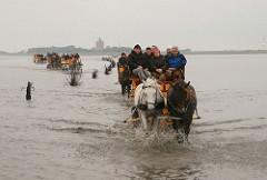 Von zwei Pferden gezogene und mit Fahrgästen dicht besetzte Wattwagen fahren durch das Wasser Richtung Cuxhaven - Pricken weisen den Weg - im Hintergrund die Insel Neuwerk mit dem hohen Leuchtturm
