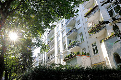 Grünes Hamburg - die Sonne scheint durch das dichte Laub von Strassenbäumen in Hamburg Eimsbüttel - mehrstöckige Wohnblocks mit Balkons.