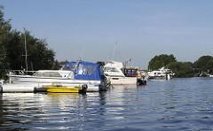 Sportboothafen hinter der Tatenberger Schleuse. Motorboote liegen am Steg der Hafenanlage.