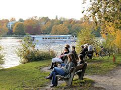Holzbänke am Ufer der Alster bei der Winterhuder Bellevue - BesucherInnen der Grünanlage sitzen in der Sonne und blicken auf das Wasser.
