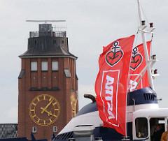 Werbefahnen des Hamburg Biers ASTRA mit Anker und Herz - Uhr und Turm der Lotsenstation Seemannshöft.