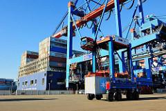 Das mit Container beladene Heck des Frachters CMA CGM CHRISTOPHE COLOMB am Burchardkai - ein Portalhubwagen transportiert einen Container zum Lagerplatz.
