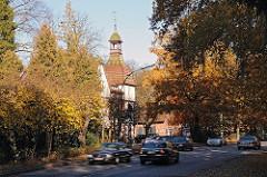 Strassenverkehr in der Wellingsbuettler Weg. Herbstliche Bäume am Wegesrand.