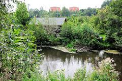 Blick über den Seevekanal zu Hochhhäusern von Hamburg Rönneburg; am Kanalufer Lauben von Schrebergärten.