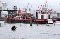 Sturmflutwarnung in Hamburg - ein Fotograf fotografiert auf dem überfluteten Altonaer Fischmarkt - ein Bunkerschiff wendet auf der Elbe.