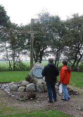 Friedhof der Namenlosen - Hamburg Neuwerk - Gedenkstein mit Kreuz, Friedhofsbesucher.