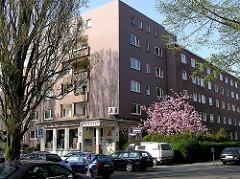 Blick zum Wohnblock mit Apotheke in der Hamburger Jarrestadt, Hanssensweg / Novalisweg (ca. 2005). Blühende Japanische Zierkirsche im Vorgarten; parkende Autos am Strassenrand.
