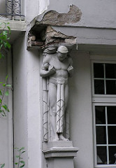 tragende Figur an einer bröckelden Hausfassade in der Sierichstrasse - Altbauten in Hamburg Winterhude.