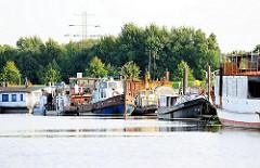 Boote am Ufer des Spreehafens - Arbeitsboote und Hausboote liege am Ufer des Hafenbeckens in Hamburg Wilhelmsburg