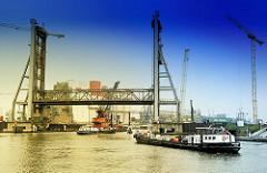 Hochgefahrene Rethehubbrücke in Hamburg Wilhelmsburg - zwei Schiffe fahren in die Rethe ein - Arbeitsschiffe und Kräne; Bau der neuen Rethebrücke.