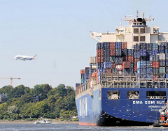 Der Containerfrachter CMA CGM BUTTERFLY läuft aus dem Hamburger Hafen aus und fährt in die Fahrrinne der Elbe ein - im Hintergrund ein Airbusflugzeug, Grossraumflugzeug BELUGA im Landeanflug.