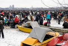 Alstereisvergnügen - Menschen auf der zugefrorenen Alster - Boote im Eis am Holzsteg am Alsterufer.