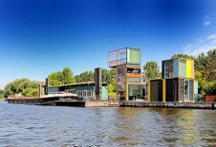 Ehemaliger Anleger für Zollschiffe am Ufer des Entenwerder Elbparks - moderne Architektur und alte Zollgebäude; eine Schute liegt am Ponton.