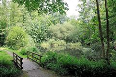 Grünanlage mit Holzbrücke über einen Bachlauf - Naherholung in Hamburg Rönneburg; Park im Stadtteil.
