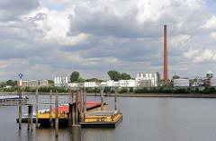 Blick über den Hamburger Wasserweg Reiherstieg zu Raffinerieanlagen in Hamburg Wilhelmsburg - Öltanks und hoher Fabrikschornstein - rechts der Wasserturm von Hamburg Wilhelmsburg.