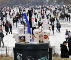 Überquellender Papierkorb beim Hamburger Alstereisvergnügen - im Hintergrund Menschen auf dem Eis der zugefrorenen Aussenalster.