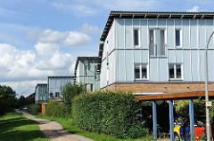 Unterschiedliche Architektur in Hamburg Neuallermöhe - einstöckige Wohngebäude mit hellblauer Fassade.