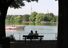 Blick auf die Aussenalster an der Fährhausstrasse - auf einer Parkbank auf dem Gelände des ehem. Uhlenhorster Fährhauses sitzen zwei Hamburgerinnen und blicken auf das Alstercabrio, das auf der Aussenalster Richtung Langer Zug fährt.