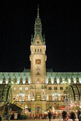 Beleuchtete Fassade und Rathausturm des Rathauses von Hamburg - ein Weihnachtsmarkt findet auf dem Rathausplatz statt.