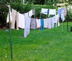 Wäsche trocknen im Freien - frisch gewaschene Wäsche hängt an einer Leine in der Sonne.