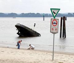 """Strandszene am Blankeneser Elbufer - Heck eines Schiffswracks, Holzdalben - Warnschild """"Gefahr des Ertrinkens durch Sog, Wellenschlag und Strömung""""."""