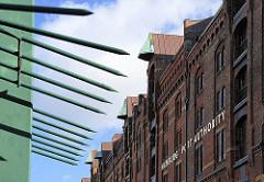 Mit Stahlspitzen bewehrter Zollzaun bei der Jungfernbrücke - goldener Schriftzug der Hamburg Port Authority HPA an der Fassade des Speichergebäudes.