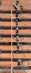 Bauarbeiter an der Fassade der entstehenden Albphilharmonie - Gerüstbauer montieren ein Baugerüst am Gebäude der Hamburger Hafencity.