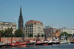 Barkassen liegen im Zollkanal vor den Kajen - im Hintergrund das Haus der Seefahrt und der Turm der ehemaligen Nikolaikirche Hamburer Innenstadt.