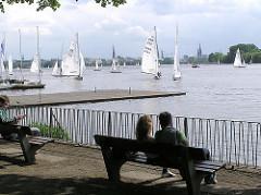 Segelboote unter Segeln auf der Aussenalster vor Hamburg Uhlenhors. Menschen sitzen auf den Parkbänken in der Sonne.