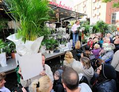 Pflanzenverkauf auf dem Fischmarkt in Hamburg - ein Marktbesucher hat mehrere Palmen erstanden und trägt sie im Karton davon.