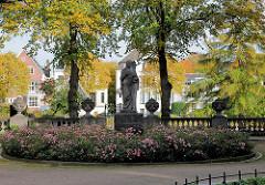 Skulptur St. Johannis im Innenhof des Johannisklosters in Hamburg Eppendorf - im Hintergrund Häuser und Bäume mit Herbstlaub am Leinpfad in Hamburg Winterhude
