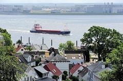 Blick über die Dächer der Häuser von Blankenese auf die Elbe - ein Containerfeeder fährt elbabwärts.