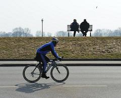 Fahrradfahren am Deich von Kirchewerder - Fahrradausflug in die Vierlande. Bank in der Sonne auf dem Elbdeich.
