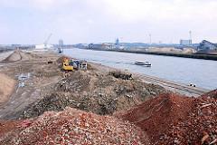 Berge Bauschutt der abgerissenen Gebäude am Versmannkai / Baakenhafen - eine Barkasse der Hamburger Hafenrundfahrt fährt Richtung Elbe.