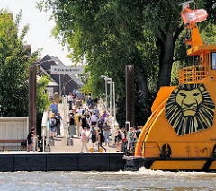 Anleger Hamburg Finkenwerder - ausgestiegene Fahrgäste gehen über die Brücke an Land; Heck des Fährschiffs.